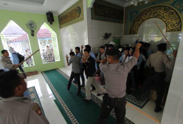 Polisi saat mengejar mahasiswa masuk Mushalla RRI Pekanbaru tanpa melepas sepatu dan memukuli pengunjukrasa